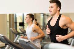 行使在健身房的踏车的微笑的人 免版税图库摄影