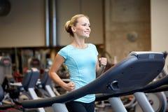 行使在健身房的踏车的微笑的妇女 免版税库存图片