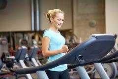 行使在健身房的踏车的微笑的妇女 图库摄影