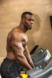 行使在健身房的踏车的肌肉黑人男性爱好健美者 免版税图库摄影