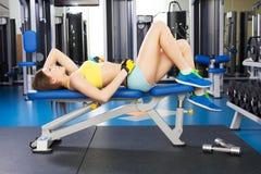 行使在健身房的年轻亭亭玉立的妇女 免版税库存照片