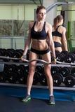 行使在健身房的年轻亭亭玉立的妇女 免版税库存图片