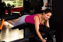 行使在健身房的说谎的腿卷毛长凳的美丽的妇女 免版税库存照片