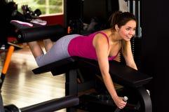 行使在健身房的说谎的腿卷毛长凳的美丽的妇女 免版税图库摄影