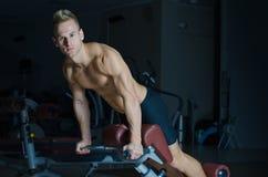 行使在健身房设备的赤裸上身的年轻人femural二头肌 库存照片