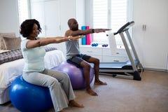 行使在健身球的夫妇在卧室 库存照片