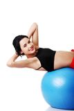 行使在健身球的妇女的侧视图 库存照片