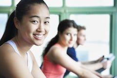 行使在健身的少妇在健身房骑自行车,看照相机 免版税图库摄影