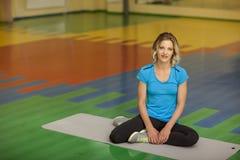 行使在健身类的席子的妇女 女性锻炼 免版税库存图片
