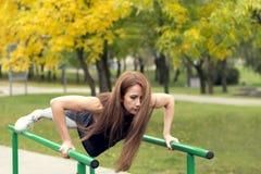 行使在双杠的美丽的女运动员,做俯卧撑 库存图片