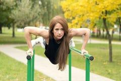 行使在双杠的美丽的女运动员,做俯卧撑 库存照片