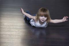 行使在地板上的小女孩 免版税图库摄影