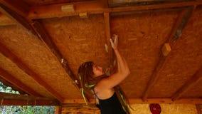 行使在室外手工制造上升的健身房墙壁的俏丽的年轻女人攀岩运动员 妇女从一举行移动到另一个 股票录像