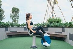 行使在户外健身房操场设备的亚裔妇女 免版税图库摄影