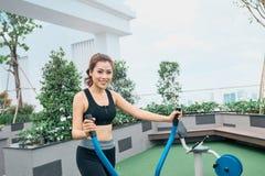 行使在户外健身房操场设备的亚裔妇女 库存图片