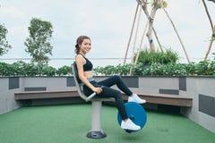 行使在户外健身房操场设备的亚裔妇女 免版税库存照片