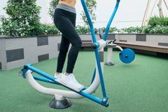 行使在户外健身房操场设备的亚裔妇女 免版税库存图片
