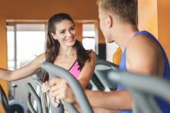 行使在有她的pa的健身机器的美丽的运动的妇女 免版税图库摄影