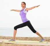 行使在海滩的正面妇女瑜伽姿势 免版税库存图片