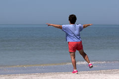 行使在海滩的资深妇女 库存照片