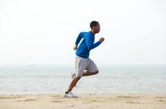 行使在海滩的年轻男性慢跑者 免版税图库摄影
