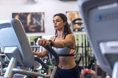 行使在省略教练员心脏训练的健身房的妇女 图库摄影
