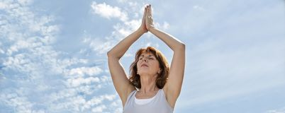 行使在祈祷的位置的美丽的成熟瑜伽妇女户外,横幅 免版税库存照片