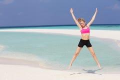 行使在美丽的海滩的妇女 免版税库存照片