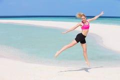 行使在美丽的海滩的妇女 免版税库存图片