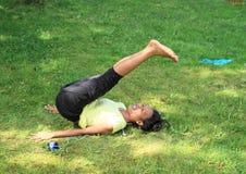 行使在草甸的女孩瑜伽 免版税库存照片