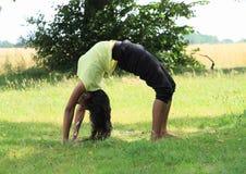 行使在草甸的女孩瑜伽 免版税图库摄影