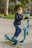 行使在街道滑雪模拟器的少妇 免版税库存图片