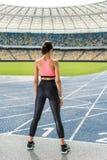 行使在连续轨道体育场的年轻女运动员 免版税图库摄影
