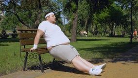 行使在长凳,室外锻炼,奋斗的肥胖年轻人减肥下来 股票视频