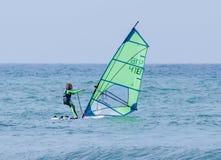 行使在风帆冲浪的女孩在地中海 库存图片