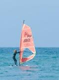行使在风帆冲浪的女孩在地中海 免版税库存图片