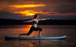 行使在paddleboard的女孩瑜伽在风景湖Velke达科的日落 库存照片