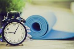行使时钟和瑜伽席子的时刻 免版税图库摄影