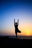 行使瑜伽日落剪影的妇女 免版税库存图片