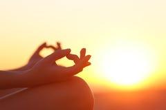 行使瑜伽的妇女手在日落 免版税库存图片