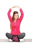行使瑜伽的少妇供以座位在席子 库存图片