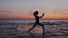 行使瑜伽的年轻体育和导电线妇女,做在海滩的战士姿势在日落天空期间 剪影亭亭玉立和适合 股票录像