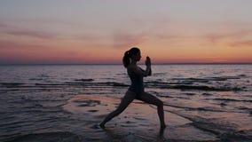 行使瑜伽的年轻女人,做在海滩的战士姿势在日落期间 一亭亭玉立和适合女孩执行的剪影 股票视频