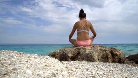 行使瑜伽的美丽的妇女思考在海滩 免版税库存照片