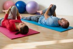 行使瑜伽的辅导员和的学生,当说谎在健身俱乐部时的席子 图库摄影