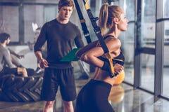 行使用trx有近教练员的健身房设备的嬉戏妇女  免版税库存照片