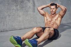 行使腹肌的男性健身式样做的仰卧起坐和咬嚼 免版税库存照片