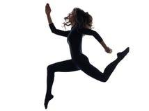 行使跑的跳跃的剪影的妇女 图库摄影