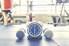行使闹钟和哑铃的时刻健身房背景 份额时间健康概念 库存照片