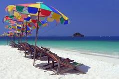 行军床在海滩的五颜六色的伞下 免版税图库摄影